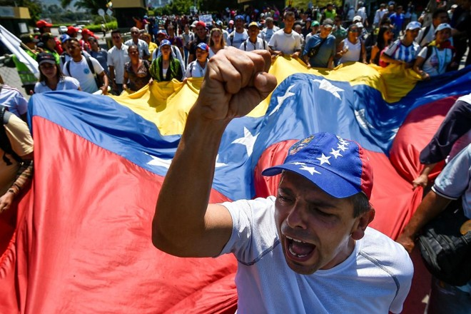 Venezuelanos participam de um protesto contra Nicolas Maduro na ponte internacional Simon Bolivar em Cúcuta, na Colômbia, na fronteira com a Venezuela, em 15 de fevereiro de 2019 | LUIS ROBAYO/AFP
