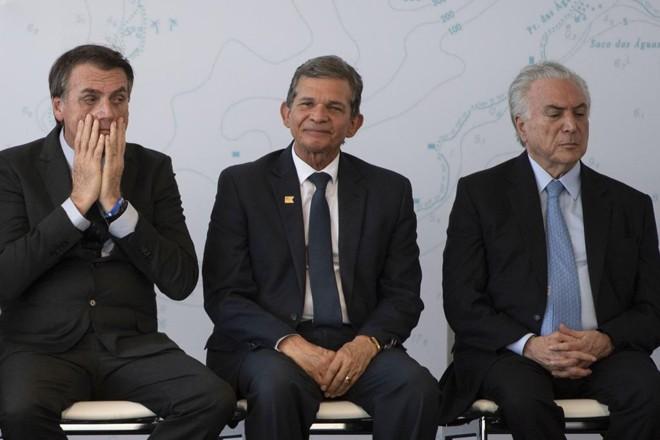 General Joaquim Silva e Luna, novo diretor da Itaipu, sentado entre Jair Bolsonaro e Michel Temer. | MAURO PIMENTEL/AFP