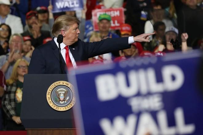 """Presidente Donald Trump em um comício em El Paso, Texas, na fronteira com o México. Apoiadores seguram cartazes onde se lê""""Construa o muro""""   JOE RAEDLE/AFP"""