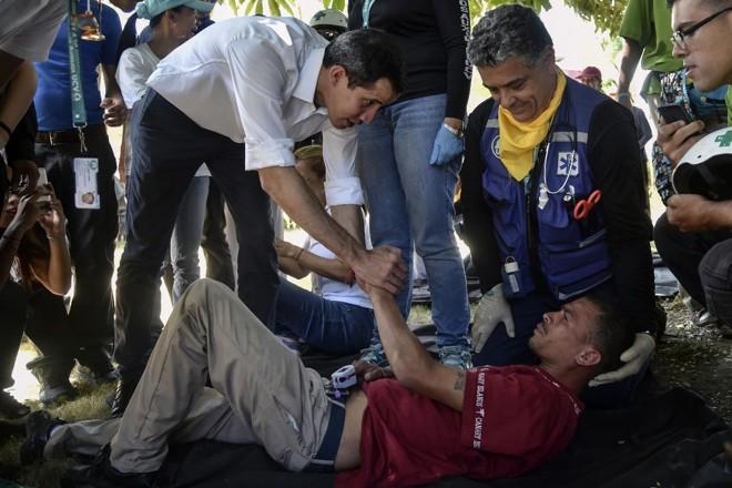 """Juan Guaido cumprimenta um voluntário do movimento """"Ajuda e Liberdade da Coalizão Venezuela"""", que desmaiou durante uma manifestação em Caracas   YURI CORTEZ/AFP"""