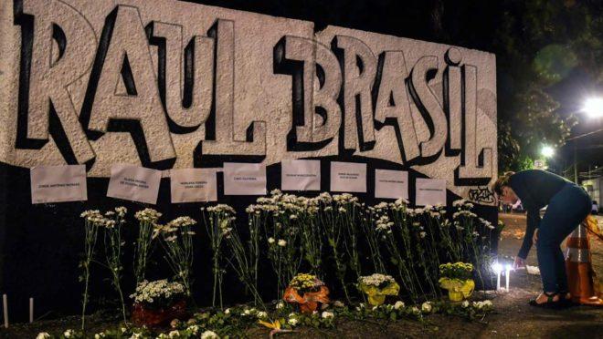 Uma mulher acende uma vela em frente à escola pública Raul Brasil. (Foto de NELSON ALMEIDA / AFP)