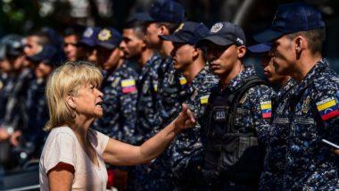 Uma mulher discute com um policial antes de uma manifestação convocada por líderes sindicais para exigir proteção trabalhista contra a demissão de funcionários públicos em Caracas, 19 de março de 2019. A manifestação foi cancelada devido ao grande deslocamento de forças de segurança nas ruas. Foto de Ronaldo SCHEMIDT / AFP