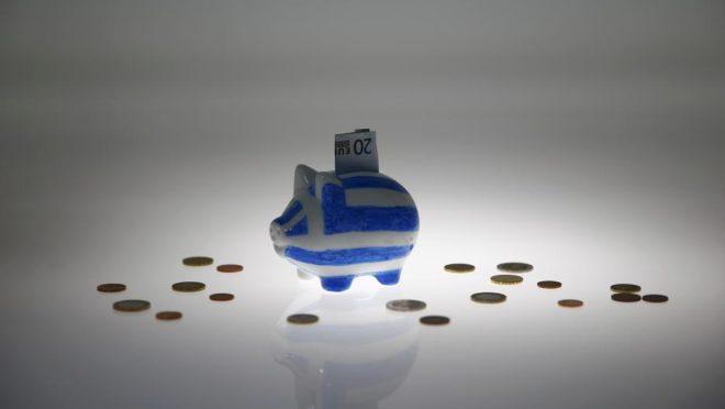 Um porquinho pintado nas cores da bandeira grega com uma nota de 20 euros