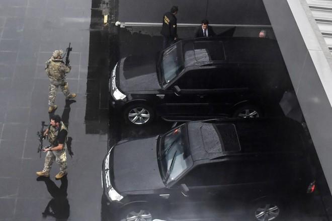 Michel Temer (no alto, à direita), entra no carro da Polícia Federal em que seria conduzido ao avião que o levou ao Rio de Janeiro.   Nelson Almeida/AFP