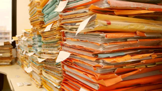 Pilha de processos parados em fórum. Burocracia. Papelada.