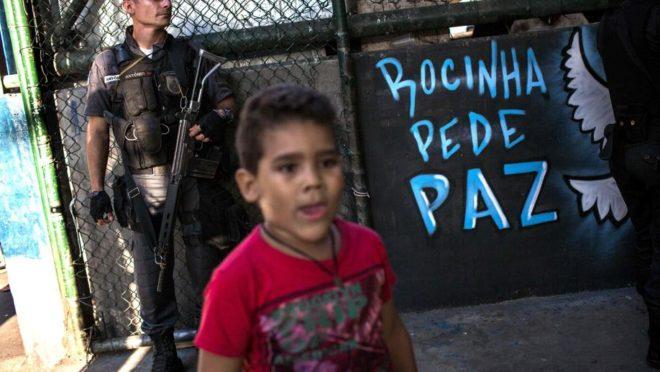 Uma criança passa enquanto um Policial militar vigia favela da Rocinha, no Rio de Janeiro, Brasil (26 de setembro de 2017). (FOTO: Mauro PIMENTEL/AFP)