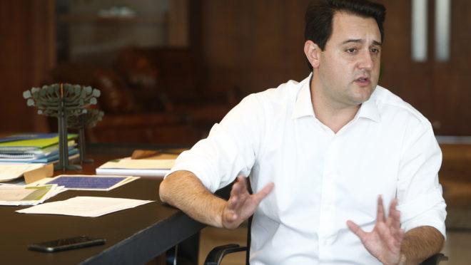 Ratinho Junior ao lado de sua mesa de trabalho no Palácio Iguaçu.