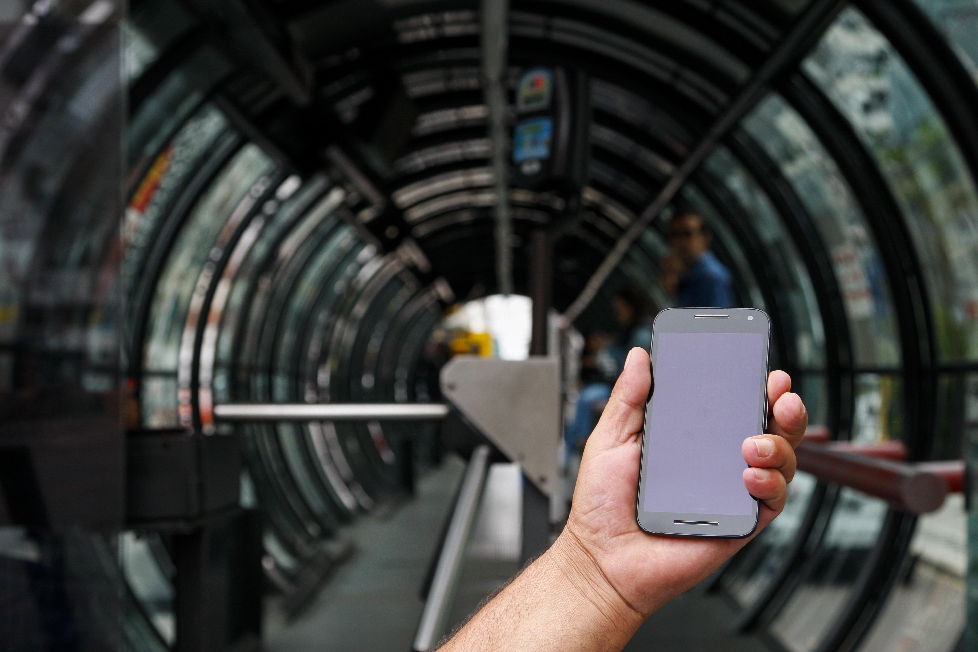celular em uma mão em frente à estação-tubo em Curitiba