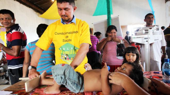 Técnico de enfermagem de Manaus atende criança cuja mãe recebe benefício do Bolsa Família.