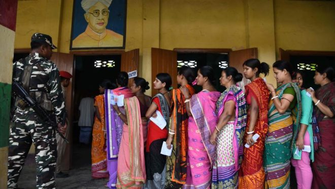 Eleitoras indianas formam fila para votar  enquanto guardas fazem a segurança na vila Amoni, durante as eleições gerais da Índia, em 11 de abril. Foto: Biju Boro / AFP