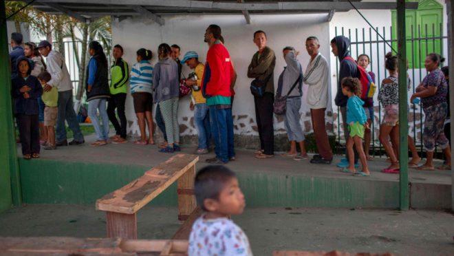 Fila de venezuelanos para pegar o café da manhã em Pacaraima, Roraima.