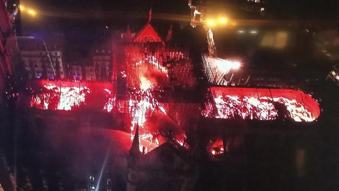 Imagem transmitida pela televisão mostra vista aérea da catedral de Notre-Dame durante o incêndio desta segunda-feira (15)