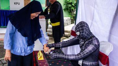 Funcionários das eleições na Indonésia vestidos de super-heróis fazem o registro de eleitores em uma seção eleitoral de Surabaya, 17 de abril. Foto:  Juni Kriswanto / AFP