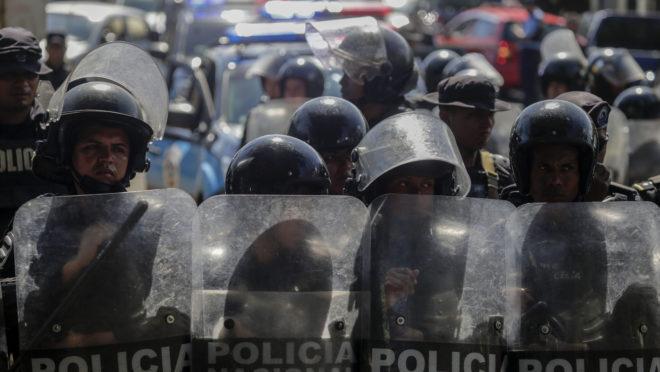 Polícia de choque ao lado de um estacionamento onde manifestantes da oposição protestam contra o governo, em 17 de abril de 2019 | Foto: INTI OCON / AFP