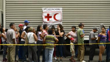 Fila de pessoas para receber água da Cruz Vermelha em Caracas na Venezuela.