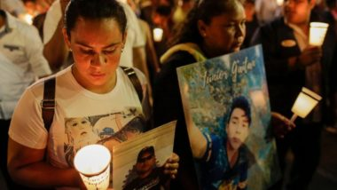 """Pessoas seguram velas e fotos de parentes que morreram durante os protestos do ano passado na procissão """"El Silencio"""" na Quinta-Feira Santa, 18 de abril. Foto: Inti Ocon / AFP"""