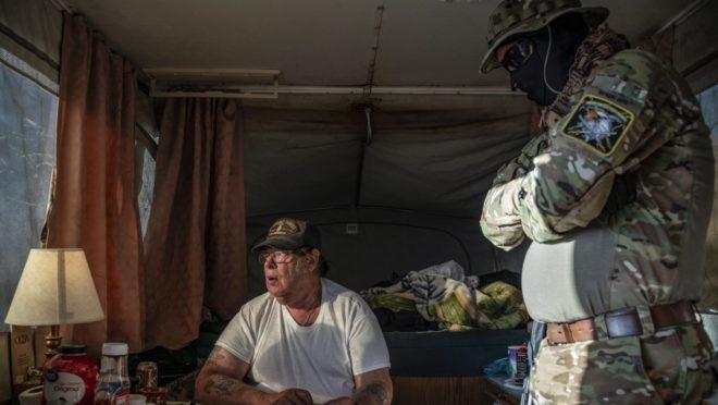 """Nesta foto de 20 de março de 2019, Larry Mitchell Hopkins, ou """"Striker"""" (à esquerda), o líder da milícia UCP no estado americano do Novo México, fala com Viper no acampamento enquanto discutem logística em um chat do grupo. Eles usavam codinomes para proteger a sua identidade. Foto: Paul Ratje / AFP"""