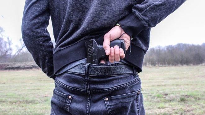 Home empunha arma escondida na cintura. Foto: Pixabay