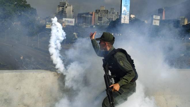 Membro da Guarda Nacional Bolivariana que agora apoia Juan Guaidó lança uma bomba de gás lacrimogêneo durante um confronto com guardas leais a Nicolás Maduro em frente à base militar de La Carlota em Caracas, em 30 de abril de 2019 | Foto: YURI CORTEZ / AFP