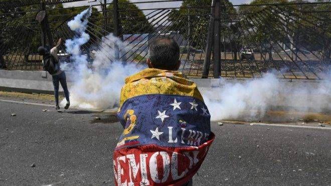 Confronto entre manifestantes da oposição e soldados leais ao ditador Nicolás Maduro após tropas se juntarem à campanha do presidente interino Juan Guaidó, nos arredores da base militar La Carlota em Caracas, 30 de abril. Foto: Federico Parra / AFP