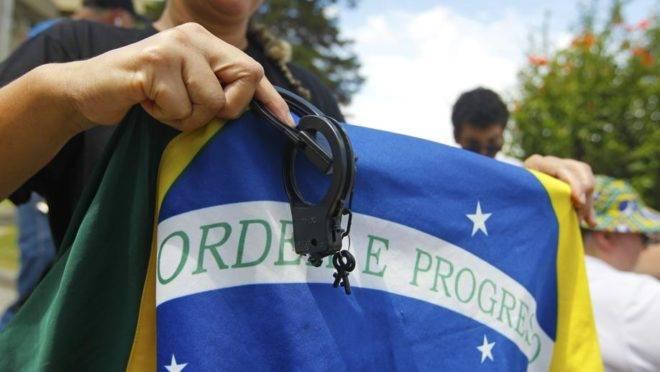 Manifestante segura bandeira do Brasil e algemas em frente ao TRE-PR, em Curitiba.