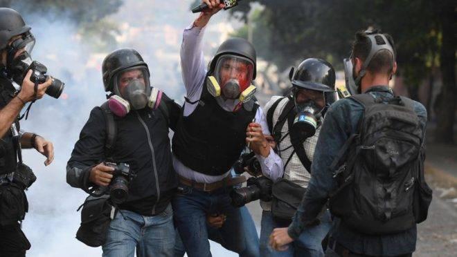 O jornalista venezuelano Gregory Jaimes (ao centro), do canal VPITV, é ajudado por colegas após ser ferido durante o confronto entre manifestantes e forças do regime de Maduro em Caracas, 1 de maio
