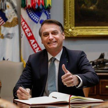 O presidente da República, Jair Bolsonaro, faz gesto de positivo.