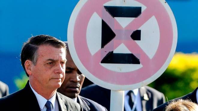 O presidente Jair Bolsonaro ao lado de uma placa de trânsito (proibido parar e estacionar)