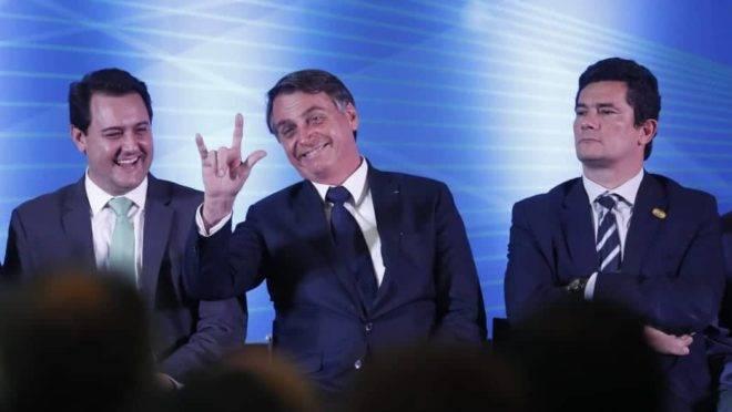 Jair Bolsonaro, entre Ratinho Jr e Sergio Moro, durante solenidade no Paraná.