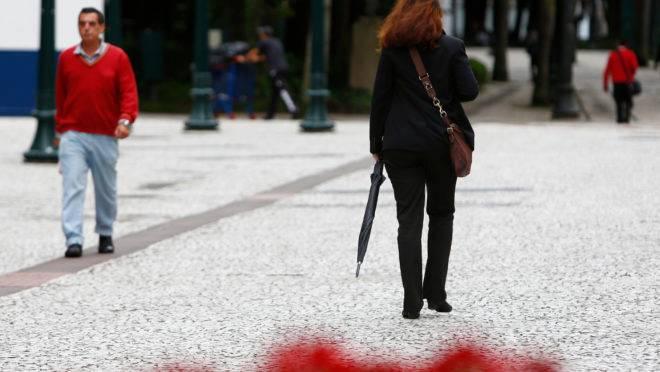 Imagem mostra uma mulher caminhando pela rua XV de Novembro, em Curitiba. Ela usa blusa fechada, bolsa na transversal e segura um guarda-chuva. Ela está caminhando, de costas para a foto. Faz frio e nublado.