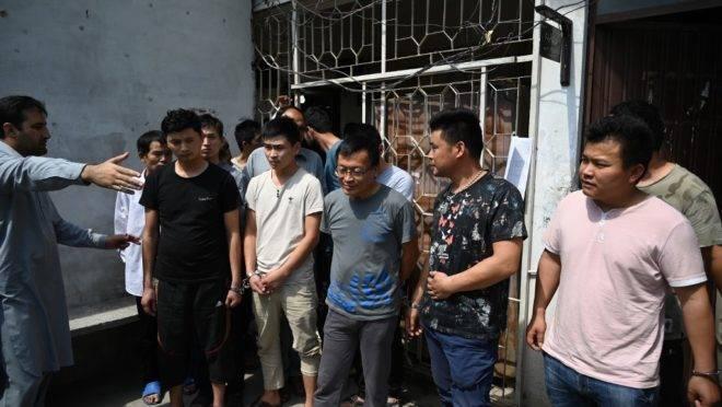 Um funcionário da Agência Federal de Investigação do Paquistão leva cidadãos chineses detidos e algemados para comparecer perante um tribunal por suposto envolvimento em uma rede de tráfico para atrair mulheres do Paquistão para casamentos falsos, forçando-as à prostituição na China, em Islamabad, em 9 de maio de 2019. O Paquistão prendeu pelo menos oito cidadãos chineses por supostamente atrair jovens paquistanesas para casamentos falsos e depois forçá-las à prostituição na China, confirmaram as autoridades à AFP em 7 de maio.