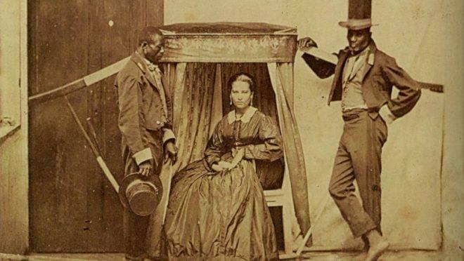 Mulher sendo carregada por escravos numa liteira na década de 1860.