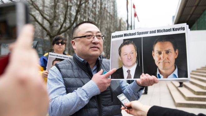 Louis Huang, da Vancouver Freedom and Democracy for China, segura fotos dos canadenses Michael Kovrig e Michael Spavor, presos na China, em Vancouver, em 6 de março de 2019