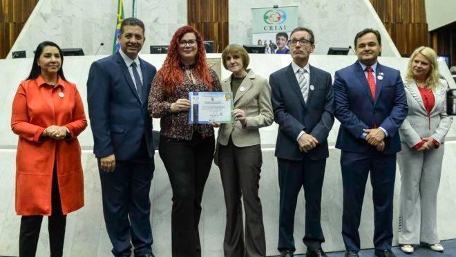 Ana Gabriela Simões Borges, Superintendente do Instituto GRPCom, recebe a homenagem dos membros da CRIAI.