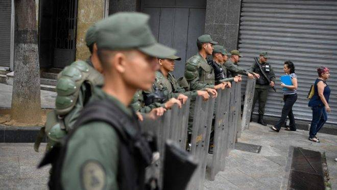 Membros da Guarda Nacional Bolivariana bloqueiam o acesso da imprensa ao Palácio Legislativo Federal, sede dos dois parlamentos da Venezuela, a Assembleia Nacional (oposicionista) e a Assembleia Nacional Constituinte (chavista), em Caracas, 28 de maio