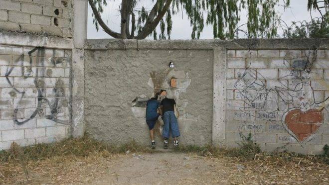 Duas crianças saem por um buraco no muro na escola San Alberto Hurtado, em La Vega, Caracas, Venezuela, 16 de abril