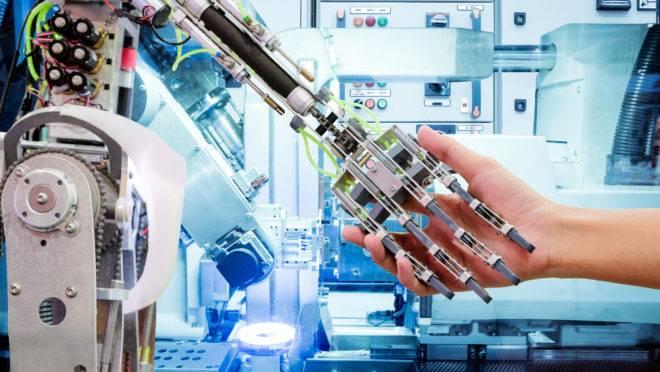 Robô segura uma mão humana.
