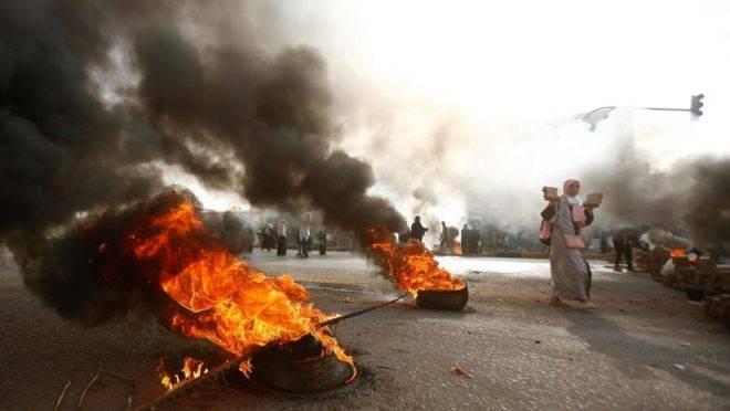 Manifestante sudanesa caminha perto de pneus em chamas enquanto forças militares tentam dispersar uma ocupação de manifestantes em frente à sede do Exército na capital, Cartum, 3 de junho