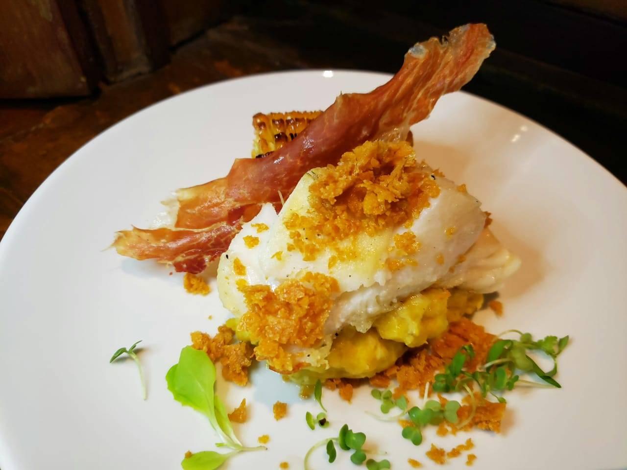 <em>Lombo de bacalhau grelhado em forno a lenha, acompanhado de guisado de banana-da-terra, milho tostado e farofa crocante de milho</em>.