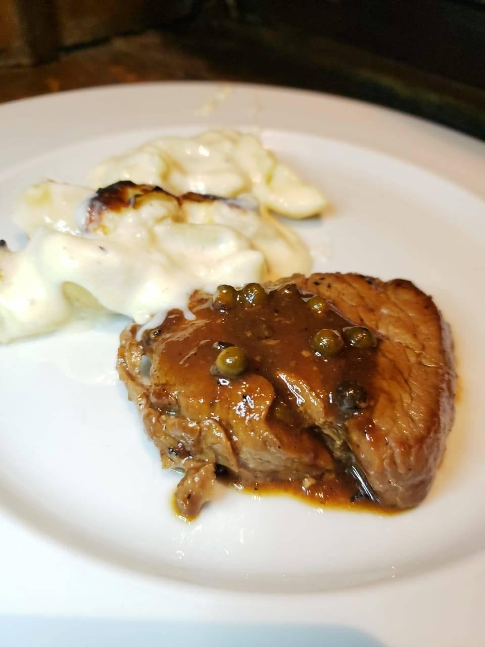 <em>Mignon grelhado no forno a lenha ao molho poivre vert, acompanhado por batatas gratinadas ao queijo Gruyère</em>.