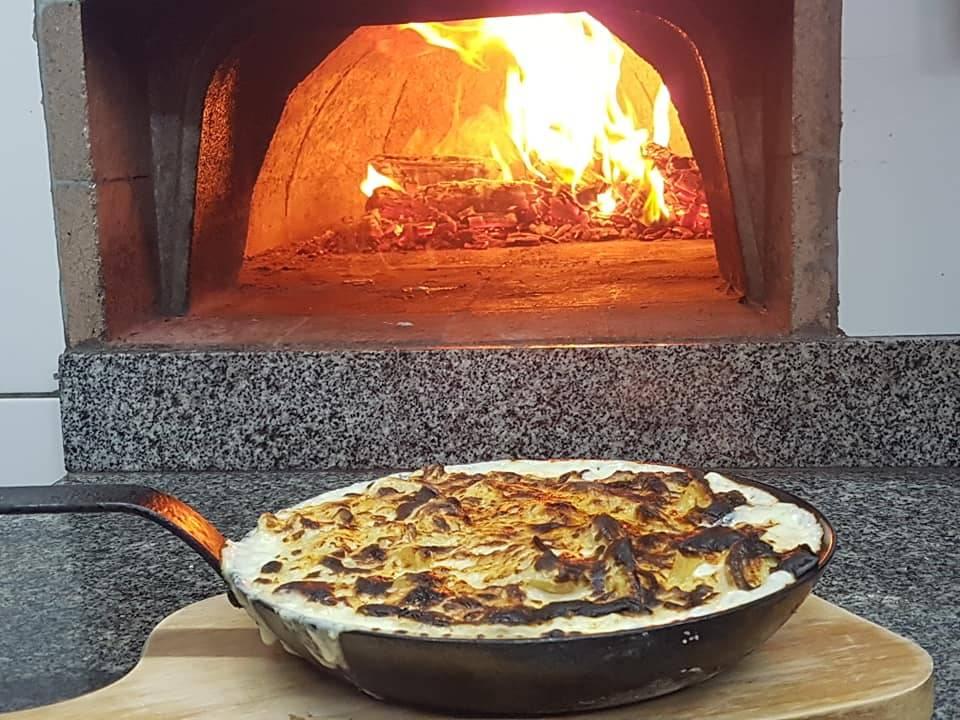 As batatas com gruyére devidamente tostadas, na boca do forno à lenha do Armazém Santo Antônio.