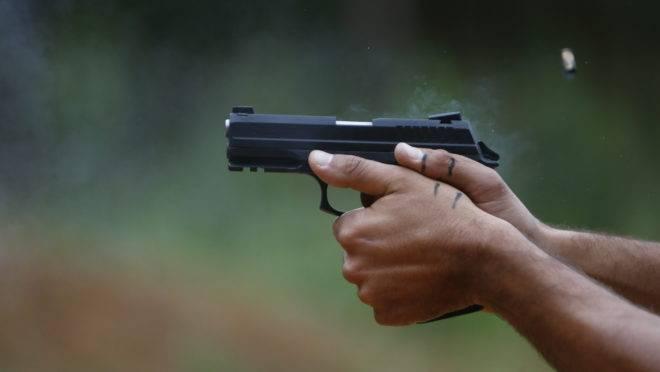 Pistola nas mãos de atirador.