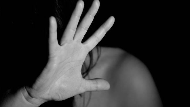 Mulher se protege de agressão usando uma das mãos