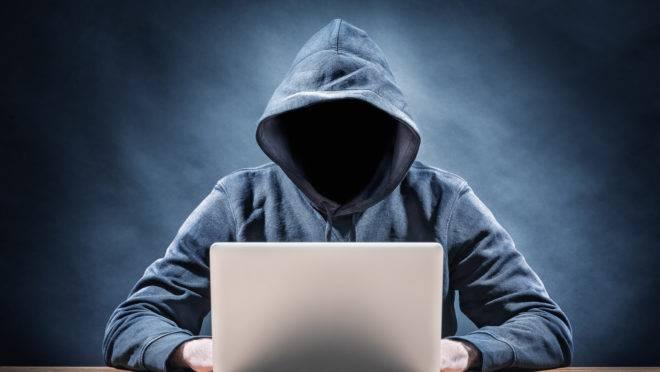 Pessoa com rosto encoberto trabalha em computador.