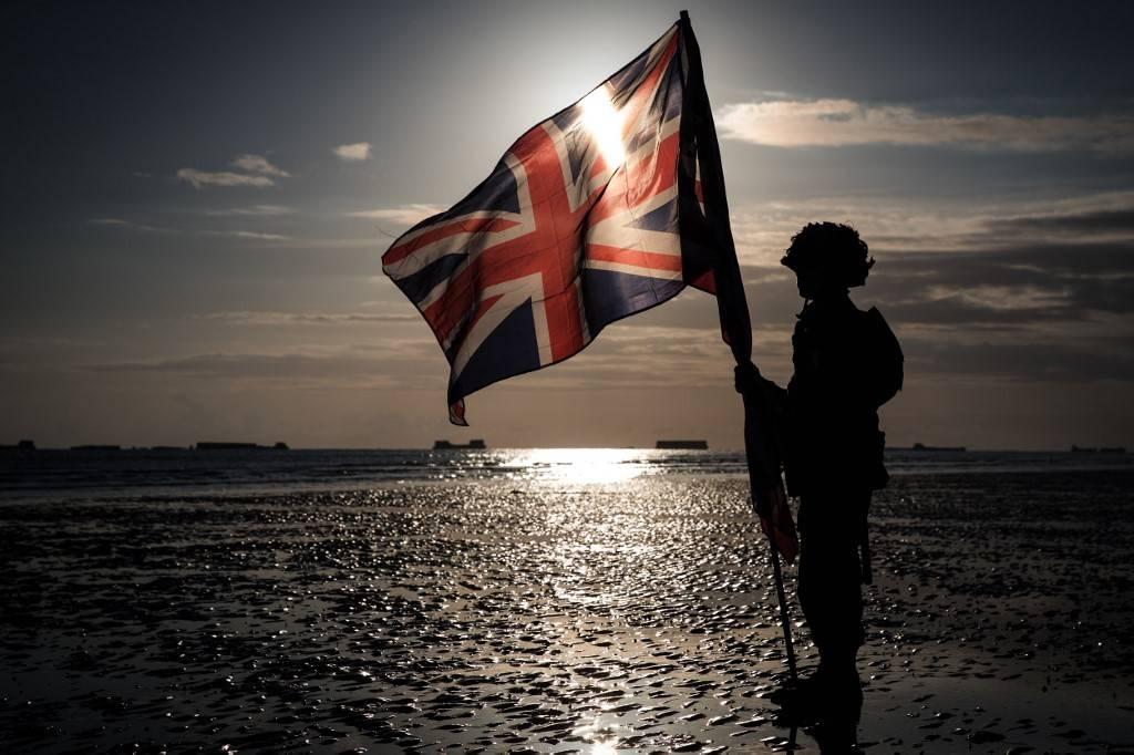 Soldado segura bandeira da Inglaterra na praia de Arromanches durante as comemorações pelos 75 anos do Dia D, quando os aliados desembarcaram na Normandia na Segunda Guerra Mundial.