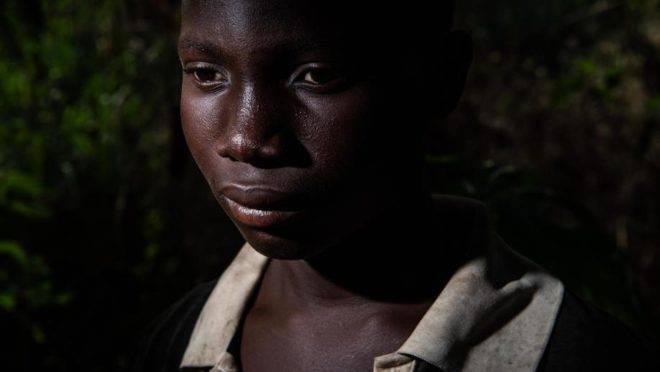 Abou Ouedrago, 15 anos, é um de muitos meninos nas fazendas de cacau que dormem em cabanas na floresta, passam os dias fazendo trabalho manual pesado e não frequentam a escola ou veem a família