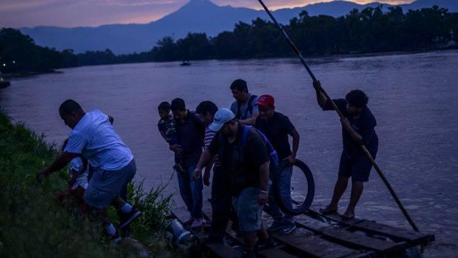 Imigrantes da América Central cruzam um rio no México, rumo aos Estados Unidos.