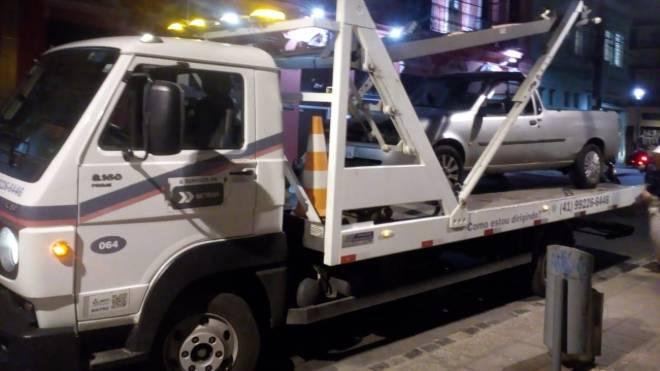 Carro Ford Courier sendo rebocado no Centro de Curitiba por acumular R$ 438,6 mil em dívida de multas e impostos.