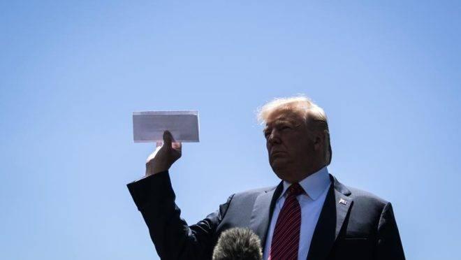 O presidente dos EUA Donald Trump mostra um documento que seria uma página do acordo ainda não revelado entre Estados Unidos e México em um jardim da Casa Branca, Washington, 11 de junho