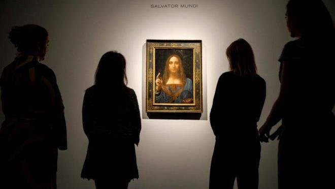 """Nesta foto de 22 de outubro de 2017, funcionários da Christie's observam a pintura """"Salvator Mundi"""", de Leonardo da Vinci, em Londres, antes de ser arrematada por US$ 450 milhões. O quadro estaria agora no iate do príncipe herdeiro da coroa saudita, Mohamed bin Salman"""